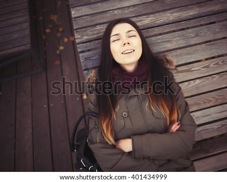 Portrait of young hipster girl wearing grey parka coat and marsala scarf lying in calm on a bench. Good mood, happy facial expression - stock photo
