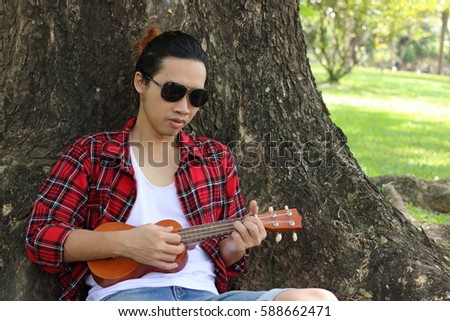 Portrait of young hipster man playing ukulele on nature background.