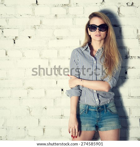 Portrait of Young Hipster Woman on White Brick Wall Background. Trendy Casual Fashion Concept. Street Style Outfit. Toned Instagram Styled Photo. - stock photo