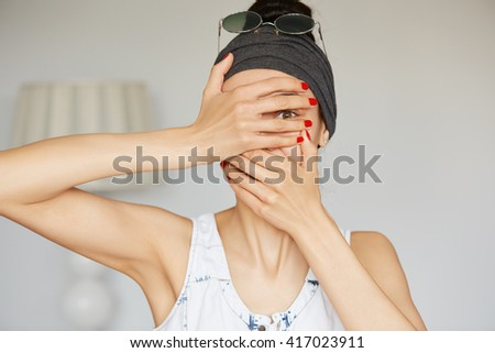 Portrait of young hipster woman peeping at the camera through her fingers. Picture of embarrassed female looking through her hands covering her face isolated against home interior background - stock photo