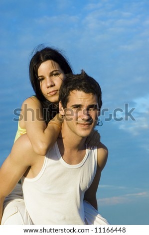 Portrait of young hispanic couple in piggyback outdoors