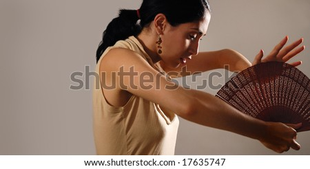 Portrait of young hispanic flamenco dancer woman holding traditional fan - stock photo