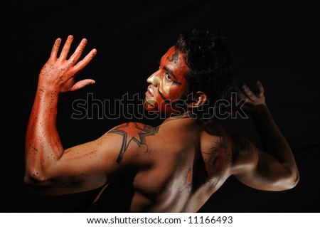 Portrait of young hispanic man with artistic bodypaint drawing - stock photo