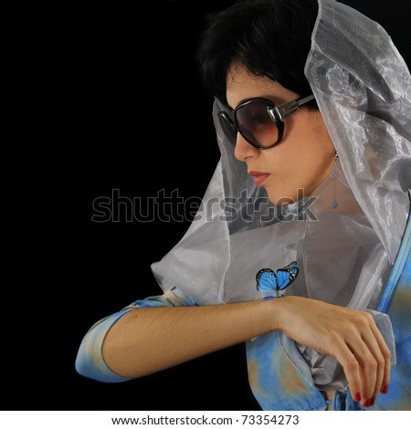 Portrait of young hispanic model wearing sunglasses holding blue butterfly isolated on black - stock photo