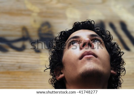 Portrait of young hispanic teen boy against grunge background - stock photo