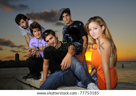 Portrait of young hispanic trendy team posing outdoors at sunset - stock photo