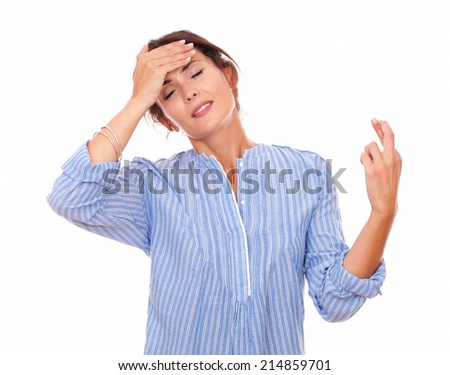 Portrait of young hispanic woman on blue blouse with closed eyes crossing her fingers while standing on isolated studio - stock photo
