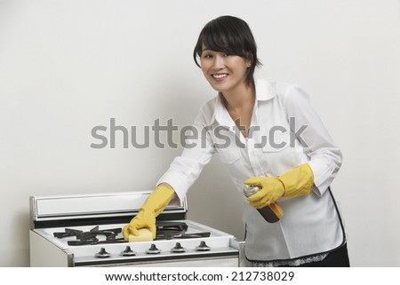 Portrait of young housemaid cleaning stove against gray background - stock photo