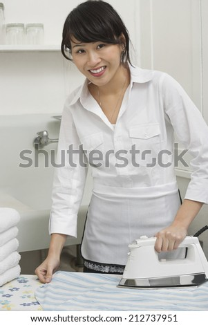 Portrait of young housemaid ironing shirt - stock photo