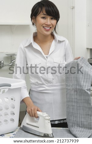 Portrait of young housemaid ironing trousers - stock photo