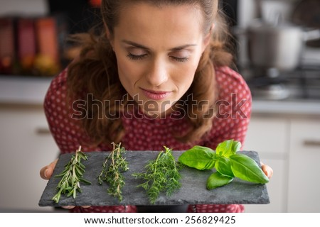 Portrait of young housewife enjoying fresh spices herbs - stock photo