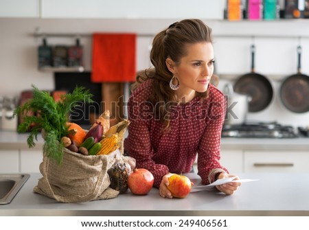 Portrait of young housewife with checks after grocery shopping - stock photo