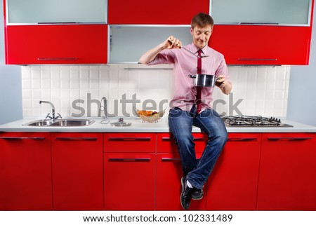 Portrait of  young hungry man filching  pan with soup on red kitchen