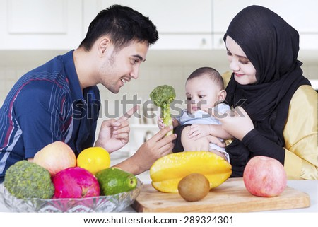 Portrait of young husband with his wife giving healthy food on their baby in the kitchen
