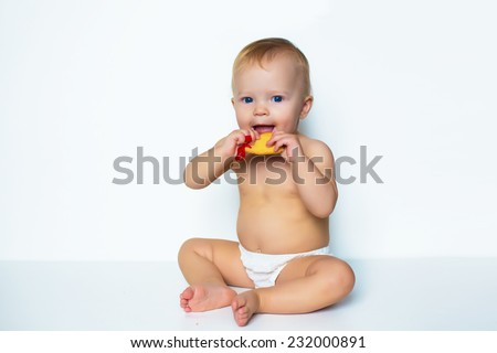 portrait of young infant adorable baby girl sitting on white eating christmas cookie - stock photo