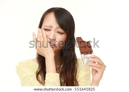 portrait of young Japanese woman suffers from toothache on white background