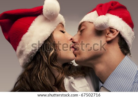 Portrait of Young kissing couple in Christmas hats - stock photo