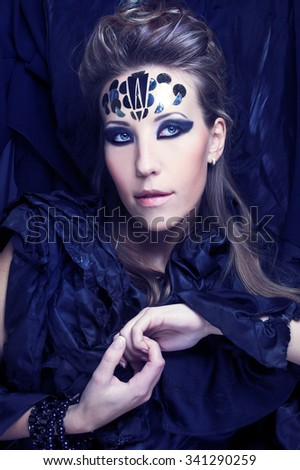 Portrait of young lady in black and with artistic visage with spangles.