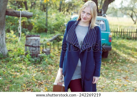 portrait of young lady in retro overcoat with vintage suitcase waiting in autumn park copy space background