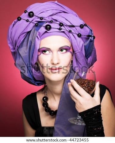 Portrait of young lady in violet turban witn cup of cafe seeds in her hand