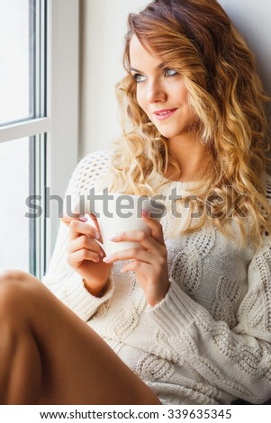 Portrait of young lady wearing white pullover sitting on a windowsill
