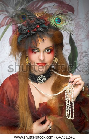 Portrait of young lady with beads and with creative make-up.