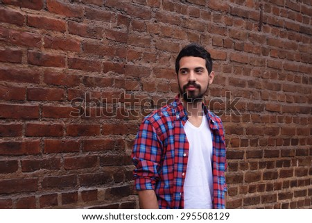 Portrait of young latin man against a brick wall.  - stock photo
