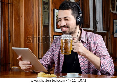 Portrait of young latin man drinking beer with headphones and digital tablet at a bar. Indoors.