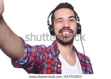 Portrait of young latin man taking selfie with black headphones. Isolated white background.
