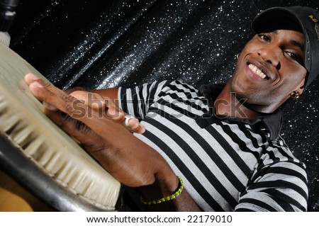 Portrait of young latino percussionist playing african drums - stock photo