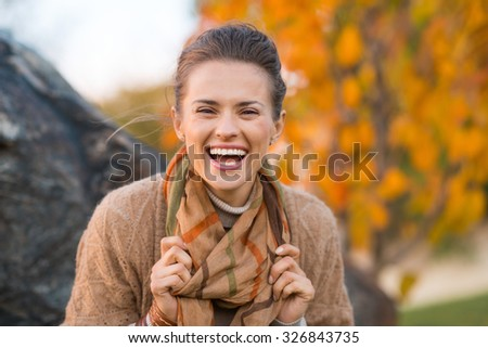 Portrait of young laughing brunette woman relaxing in beautiful evening in autumn park - stock photo