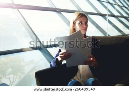 Portrait of young lovely businesswoman holding some papers or documents sitting in light office interior next to the window, business woman examining paperwork, flare sun light from the window - stock photo