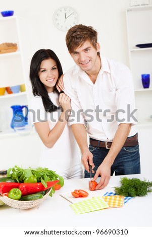 portrait of young lovely couple cooking slicing tomato in their kitchen, looking at camera woman embrace, hug happy smile - stock photo