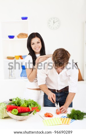 portrait of young lovely couple cooking slicing tomato in their kitchen, woman embrace, hug happy smile looking at camera - stock photo