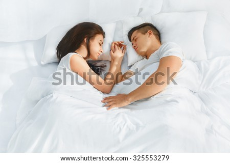 Portrait of young lovely couple sleeping in the bed on white blankets faced to each other. Healthy lifestyle. Relationships , closeness. - stock photo