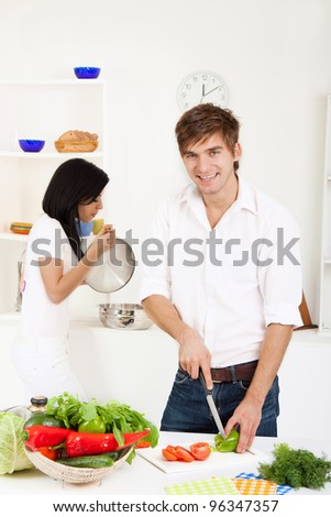 portrait of young lovely couple slicing tomato in their kitchen, man happy smile looking at camera - stock photo