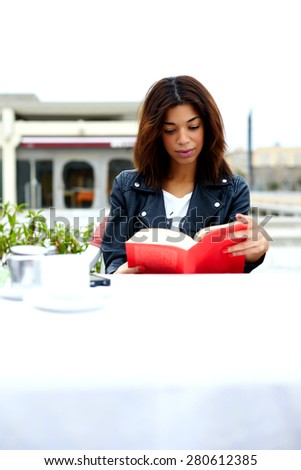 Portrait of young lovely female enjoying a good book while sitting at the table in coffee shop terrace, charming afro american woman reading novel or book during her recreation time at weekend - stock photo
