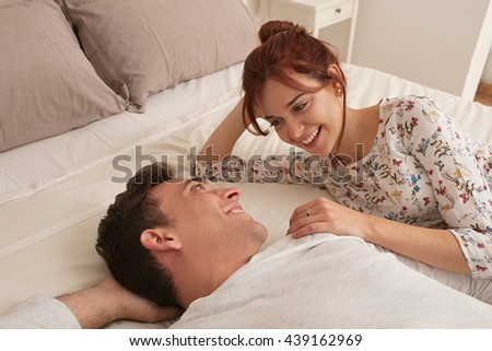 Portrait of young lovers couple laying relaxing together in bed in home interior, smiling and sharing fun moments, indoors home. Relationships lifestyle, bedroom fun with boyfriend and girlfriend. - stock photo