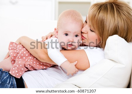 Portrait of young loving mother her newborn baby - indoors - stock photo