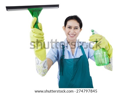 Portrait of young maid holding cleaning tools while wearing uniform, isolated on white background - stock photo