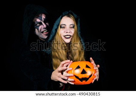 Portrait of young make up man and women holding pumpkins, isolated on black. Halloween and body art concept.