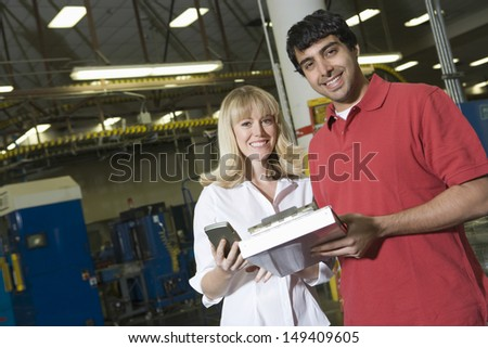 Portrait of young male and female make inventory in the newspaper factory - stock photo