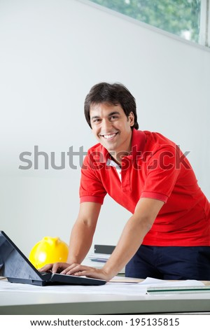 Portrait of young male architect in casual wear smiling while working on laptop - stock photo