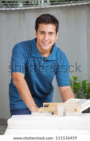 Portrait of young male architect in casual wear working on project - stock photo