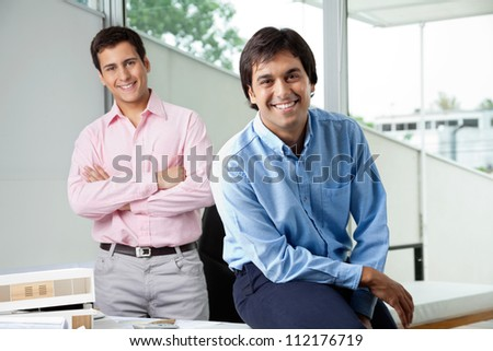 Portrait of young male architect smiling while colleague stands with arms crossed in background - stock photo