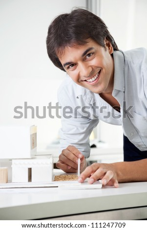 Portrait of young male architect smiling while creating a model house - stock photo