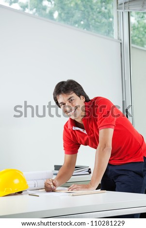 Portrait of young male architect smiling while working on blueprint - stock photo