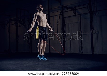 Portrait of young male athlete skipping rope - stock photo
