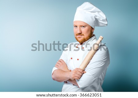 Portrait of young male chef in white uniform. Head-cook holding rolling-pin in one hand and standing against grey background - stock photo