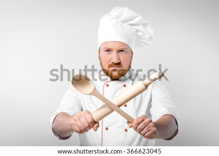 Portrait of young male chef in white uniform. Head-cook holding rolling-pin with big wooden spoon and looking strongly at camera - stock photo